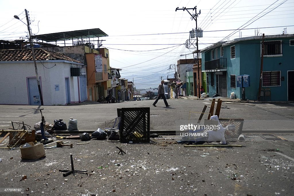 A man walks past a barricade set up by anti-government activists in San Cristobal, Tachira state, on March 6, 2014. A police officer and a civilian died Thursday during clashes in the Venezuelan capital Caracas, bringing to 20 the toll from a month of anti-government demonstrations in the divided country. AFP PHOTO/Leo RAMIREZ