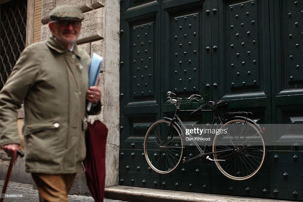 A man walks past a bicycle hanging on a doorway close to the Pantheon on March 25, 2013 in Rome, Italy.
