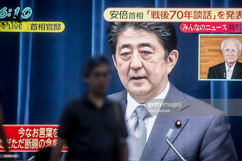 A man walks past a big screen showing a live broadcast of Japanese Prime Minister, Shinzo Abe as he delivers his WWII Anniversary Statement on August 14, 2015 in Tokyo, Japan. Japanese Prime Minister Abe delivered a war anniversary statement ahead of the anniversary of Japan's defeat in the second world war. The statement included such keywords as 'apology from the heart,' 'colonial rule,' and 'aggression.'