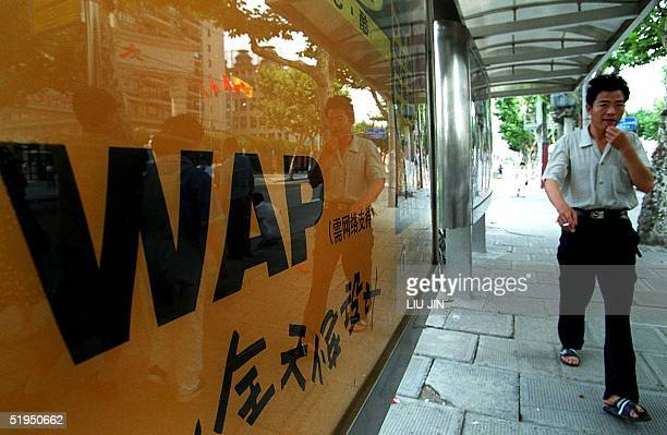 A man walks past a billboard advertisement for a WAP mobile phone at bus stop in Shanghai 29 June 2000 Chinese users of WAPcompliant cell phones can...