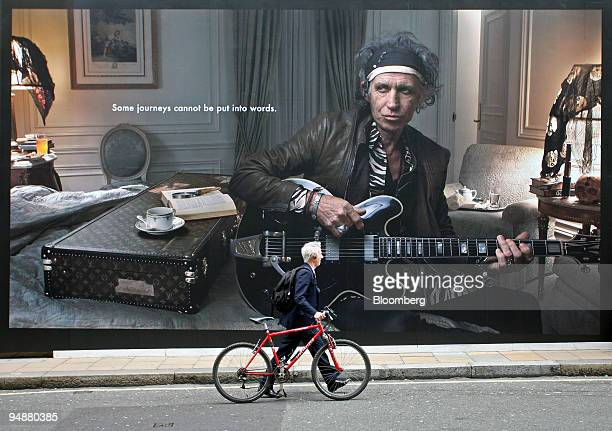 A man walks past a billboard advertisement of Keith Richards outside the Louis Vuitton store on New Bond Street in London UK on Tuesday March 4 2008...