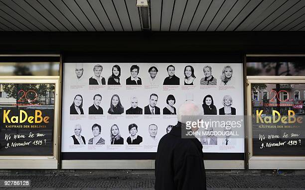 A man walks past a billboard featuring portraits of people and their recollections of the fall of the Berlin wall in 1989 at Berlin's KaDeWe...