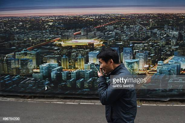 A man walks past a billboard scene of the Beijing skyline on a street in Beijing on November 12 2015 Under what Chinese leaders call the 'new normal'...