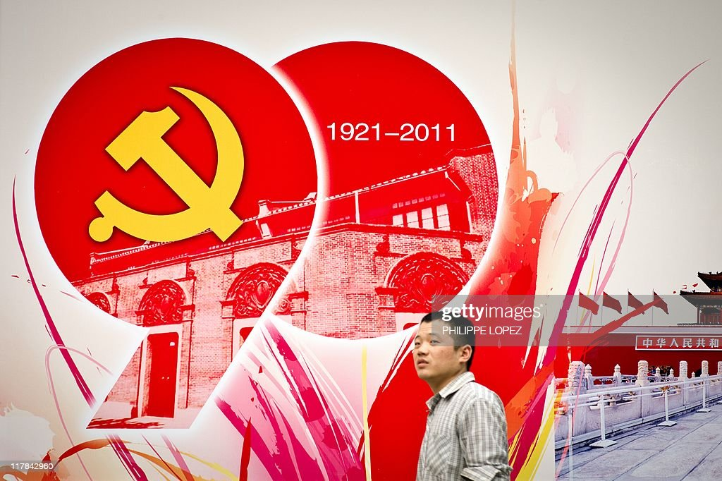 A man walks past a billboard set up as part of the celebrations of the Chinese Communist Party's 90th anniversary in Shanghai on July 1 2011 Chinese...