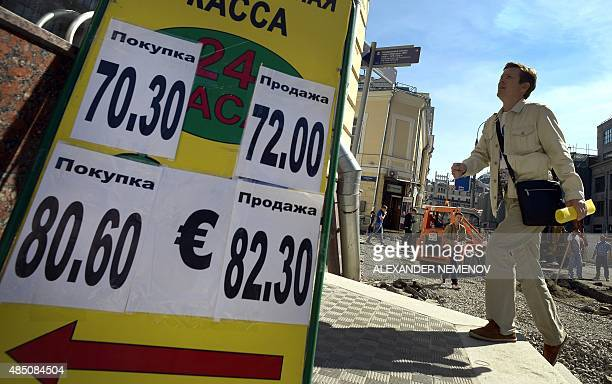 A man walks past a board listing foreign currency rates in comparison with the Russian ruble outside an exchange office in Moscow on August 24 2015...