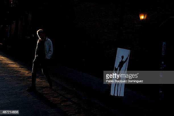 A man walks past a board with a drawing of Don Quixote on near the Convento de las Trinitarias Descalzas on April 28 2014 in Madrid Spain The author...