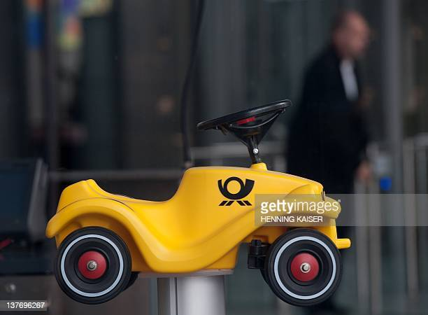 A man walks past a BobbyCar children's vehicle in Deutsche Post design at the headquarters of Deutsche Post in Bonn western Germany on January 25...