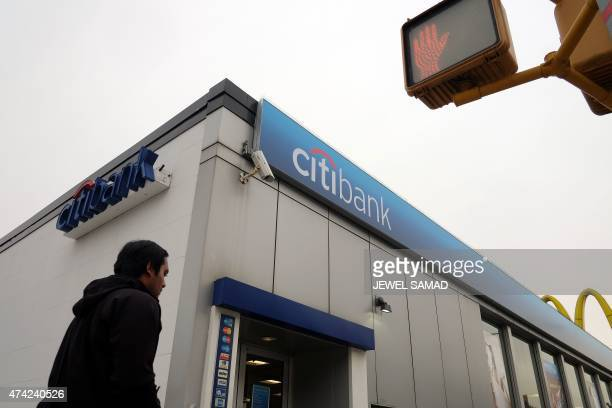A man walks past a branch of Citibank in New York on May 21 2015 US and British regulators fined six major global banks a total of nearly 6 billion...