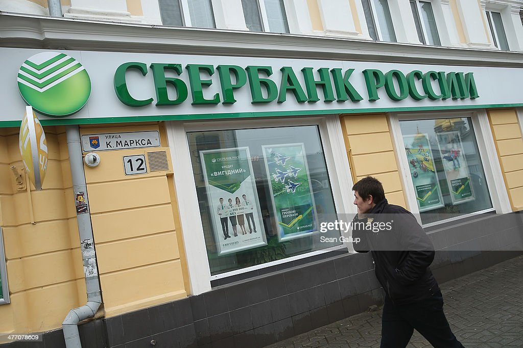 A man walks past a branch of Sberbank Rossii on March 7, 2014 in Simferopol, Ukraine. Banks in Ukraine have begun imposing limits on the amount of money individuals can withdrae per day, and both the Ukrainian hryvnia and the Russian rouble have fluctuated strongly against western currencies in the last week as tensions in Crimea have risen. The Crimean Parliament voted yesterday to hold a referendum on March 16 to determine whether Crimea shall secede from Ukraine and join Russia.