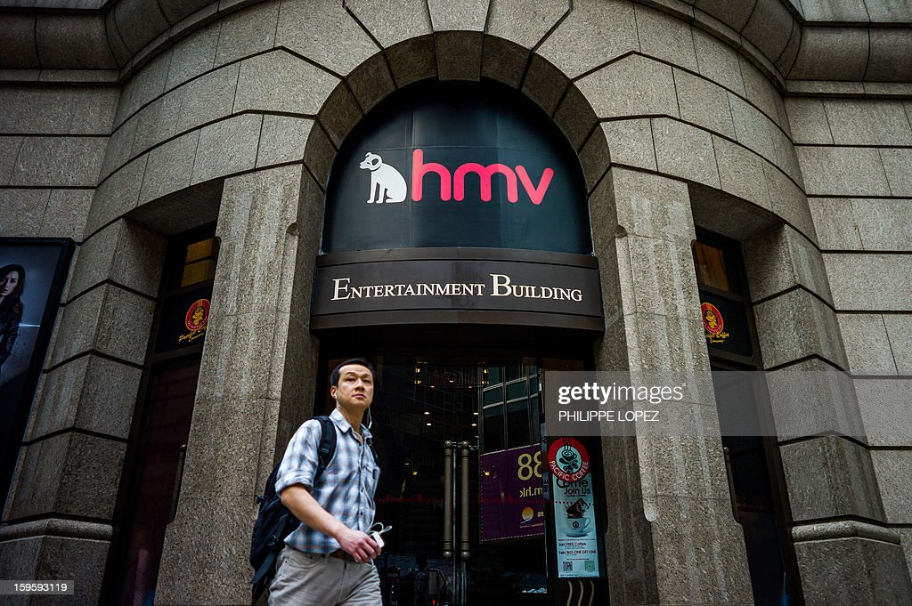 A man walks past a building housing a HMV store in Hong Kong on January 17, 2013. Iconic British music retailer HMV is fighting for survival after slumping into administration, but its boss expressed hope the high-street giant would manage to secure its future. AFP PHOTO / Philippe Lopez