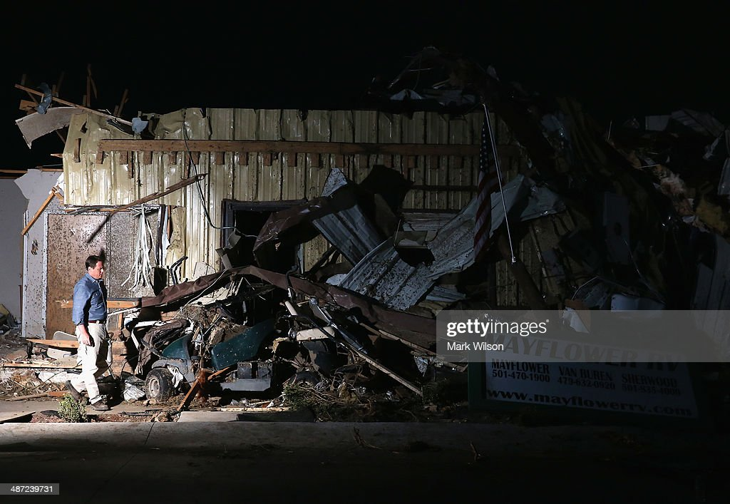 A man walks past a building that was destroyed by a tornado yesterday when it tore through the area for the second time in three years on April 28...