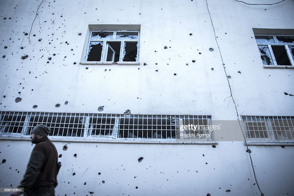 A man walks past a building which was damaged by PKK terrorists, after counter-terror operation in Cizre, the southeastern Turkish town that has seen fighting rage between security forces and PKK terrorists finished, on February 12, 2016.
