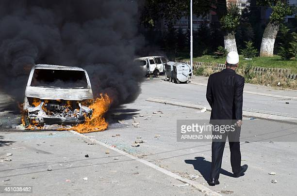 A man walks past a burning vehicle during clashes between protesters and antiriot police on June 22 2014 in the divided town of Mitrovica Kosovo...