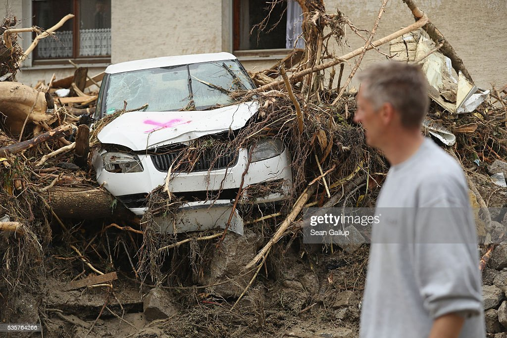 A man walks past a car smashed between rocks and torn trees in the village center following a furious flash flood the night before on May 30, 2016 in Braunsbach, Germany. The flood tore through Braunsbach, crushing cars, ripping corners of houses and flooding homes during a storm that hit southwestern Germany. Miraculously no one in Braunsbach was killed, though three people died as a result of the storm in other parts of the country.