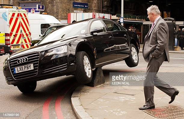 A man walks past a car that mounted a bollard near London Bridge station in central London on April 16 2012 AFP PHOTO / LEON NEAL