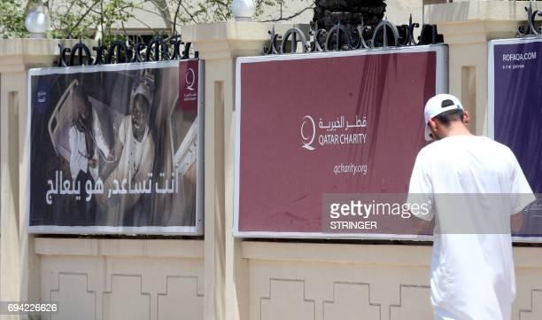 A man walks past a charity billboard in the Qatari capital Doha on June 9 2017 Saudi Arabia Egypt the UAE and Bahrain announced on June 5 they were...
