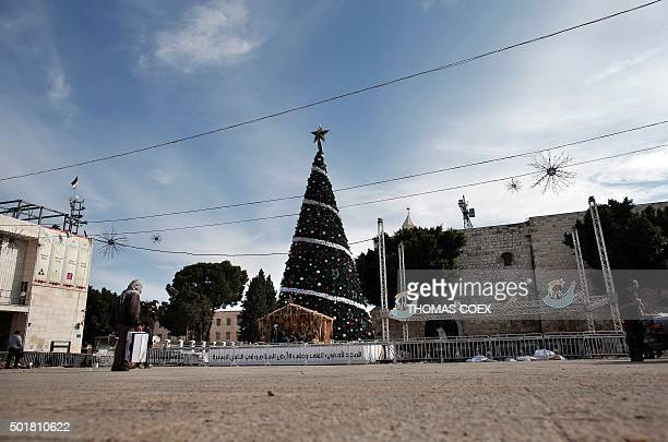 A man walks past a Christmas tree on the Manger Square near the Church of the Nativity revered as the site of Jesus Christ's birth on December 16...