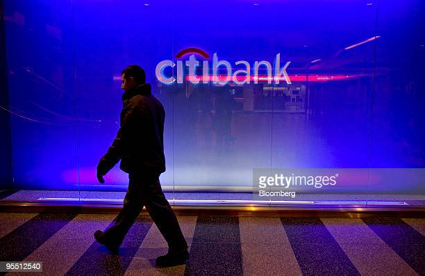 A man walks past a Citibank sign outside a branch in New York US on Thursday Dec 31 2009 US banks have tapped the Federal Reserve less as they have...