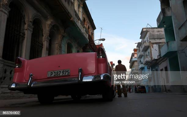 A man walks past a classic car in the old town on October 9 2017 in Havana Cuba