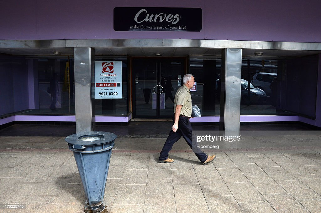 A man walks past a closed fitness club in the mining town of Kalgoorlie, Australia, on Thursday, Aug. 8, 2013. Western Australia, the nation's largest state by area with 2.6 million square kilometers (1 million square miles) of land, earned A$97 billion from minerals and energy sales in 2012, down from A$108 billion in 2011, according to government figures. Photographer: Carla Gottgens/Bloomberg via Getty Images