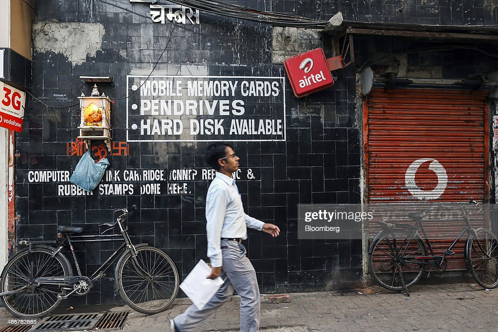 A man walks past a closed store displaying the Vodafone Group Plc logo on its shutter in Mumbai, India, on Wednesday, Jan. 29, 2014. India got bids totaling 446.1 billion rupees ($7.12 billion) on the first day of a wireless spectrum auction on Feb. 3, the third effort by the government to raise revenue from the sale of airwaves in the last 15 months. Photographer: Dhiraj Singh/Bloomberg via Getty Images