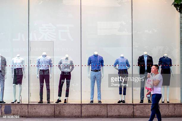 A man walks past a clothing shop window In the midst of a stock market panic in early July China issued its GDP growth of 7 percentbeating economists...