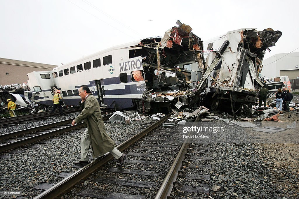 A man walks past a commuter train wreck on January 26, 2005 in Glendale, California. The wreck, involving two commuter trains carrying hundreds of passengers, reportedly occurred when one of the trains derailed after hitting a car intentionally park in a railroad crossing. The derailment left at least nine people dead and more than 200 injured.