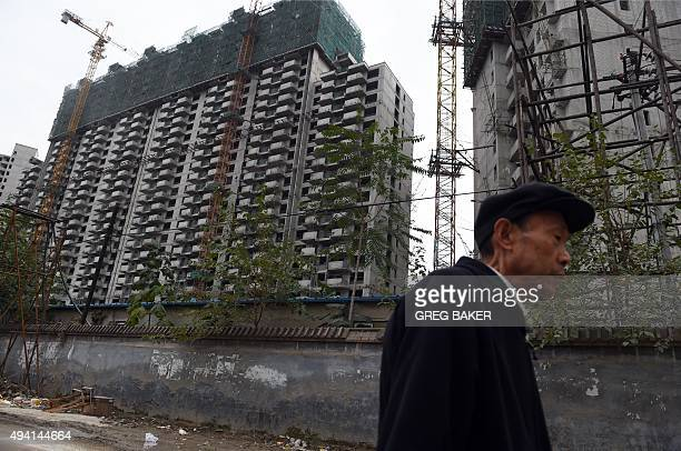 A man walks past a construction site for apartment buildings in Beijing on October 25 2015 China's leaders will gather on October 26 to hash out a...