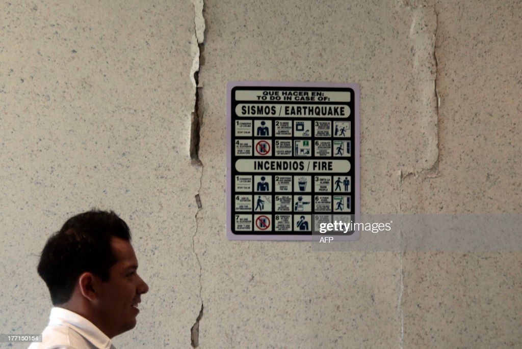 A man walks past a cracked wall during the evacuation of the Alarcon hospital in Acapulco following a 5.62-magnitude aftershock which was reported minutes after a 6.0 magnitude earthquake shook Mexico City on August 21, 2013. A strong 6.0 magnitude earthquake and an aftershock rattled Mexico on Wednesday, causing evacuations of buildings in the capital and hotels in the Pacific resort of Acapulco. The quake's epicenter has been located 17 km west of the town of San Marcos in the southern state of Guerrero, the National Seismology Center said. A 5.62-magnitude aftershock was reported 20 minutes later 14 km northeast of Acapulco, where rocks from a hill rolled into a street and some hotel facades showed cracks while tourists poured into the streets. AFP PHOTO / Pedro PARDO