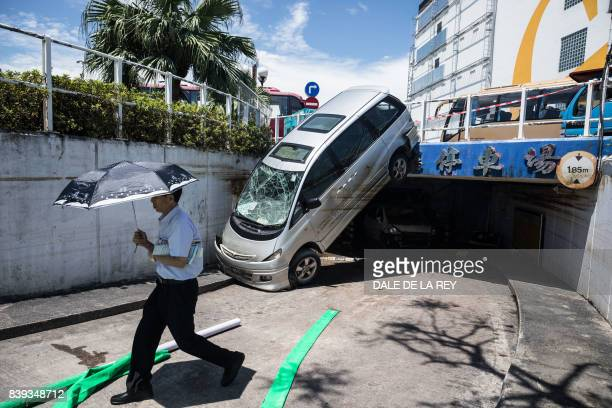 TOPSHOT A man walks past a damaged car in the aftermath of Typhoon Hato in Macau on August 26 2017 The Chinese army on August 25 joined relief...