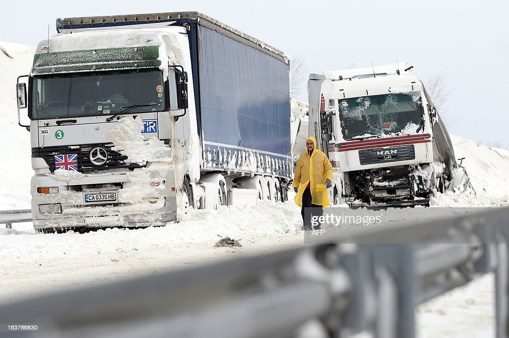 A man walks past a damaged truck at the site of an accident on the E71 motorway, nearby the Croatian, Slovenian and Hungarian borders on March 15, 2013 a day after a heavy snow storm hit the area. A cold snap that caused havoc elsewhere in Europe sent temperatures plunging and blanketed large parts of Hungary in snow, causing major transport problems and leaving tens of thousands without electricity.