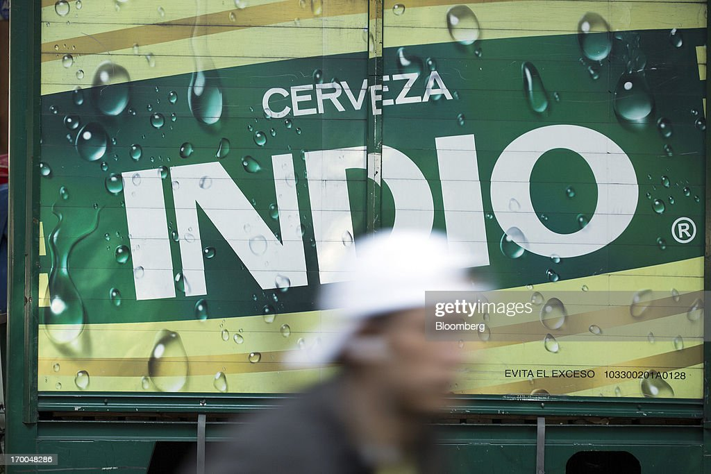 A man walks past a delivery truck operated by Cuauhtemoc-Moctezuma, a subsidiary of Heineken NV, in Mexico City, Mexico, on Thursday, June 6, 2013. Heineken NV and Grupo Modelo SAB, the dominant brewers in Mexico with brands such as Dos Equis and Corona, are nearing the end of an almost three-year-old government antitrust probe. Photographer: Susana Gonzalez/Bloomberg via Getty Images