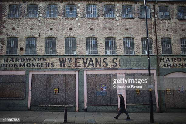 A man walks past a derelict building in Wolverhampton which has been declared the most miserable place in Britain on October 28 2015 in Wolverhampton...
