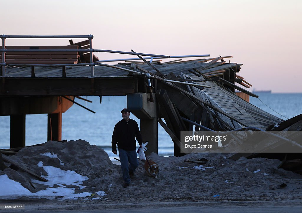 A man walks past a destroyed section of the boardwalk at the base of Lincoln Boulevard as Long Islanders continue their clean up efforts in the aftermath of Superstorm Sandy on November 9, 2012 in Long Beach, New York. New York Gov. Andrew M. Cuomo has said that the economic loss and damage to homes and business caused by Sandy could total $33 billion in New York, according to published reports.