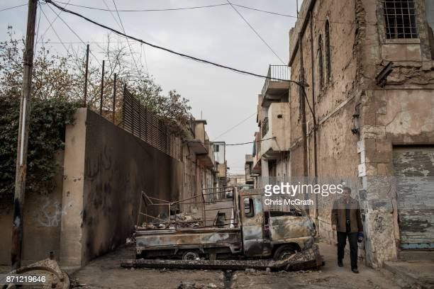 A man walks past a destroyed vehicle in West Mosul on November 6 2017 in Mosul Iraq Five months after Mosul Iraq's secondlargest city was liberated...