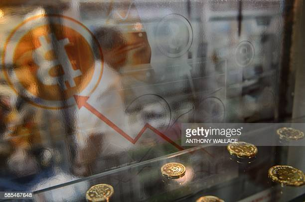 A man walks past a display cabinet containing models of Bitcoins in Hong Kong on August 3 2016 A major Hong Kongbased Bitcoin exchange has suspended...
