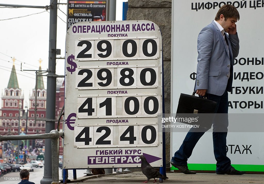 A man walks past a display of a currency exchange bureau in central Moscow on August 9 2011 The Russian ruble lost more than 25 percent of its value...