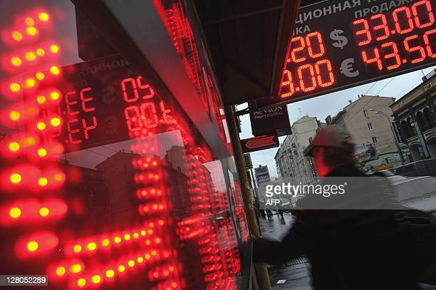 A man walks past a display of a currency exchange office in central Moscow on October 4 2011 Russia reported $187 billion in capital outflows in the...