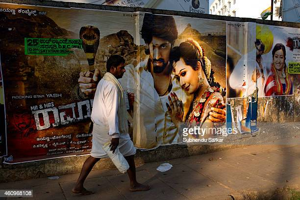A man walks past a film poster in Mysore