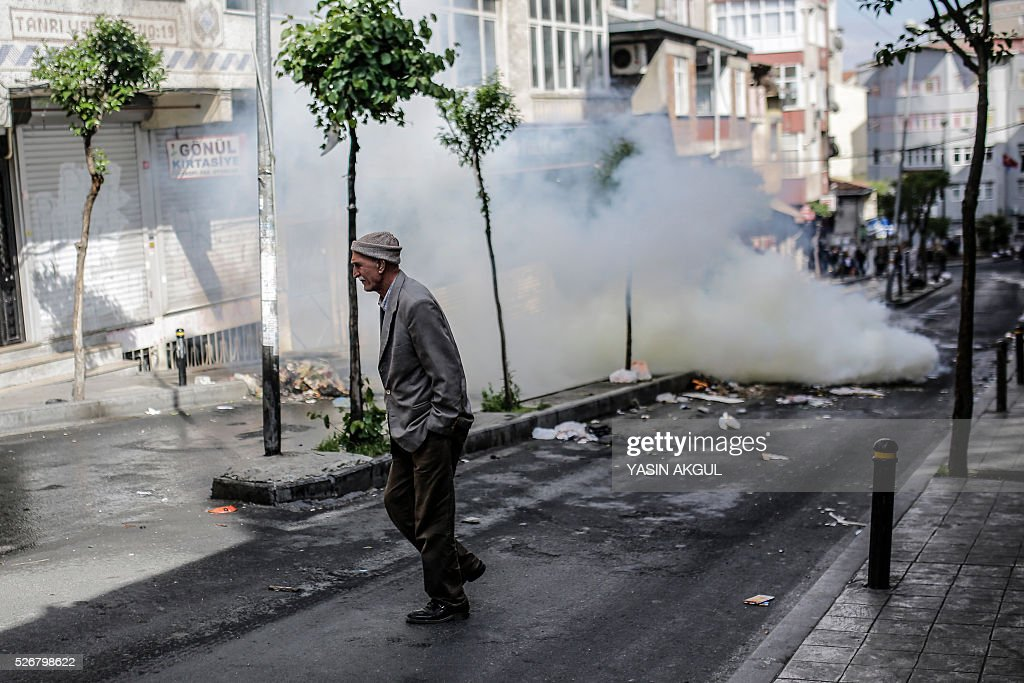 A man walks past a fire barricade during a May Day rally in Okmeydani, a district of Istanbul on May 1, 2016. Turkish labour activists and leftists marked the annual May Day holiday, with thousands of security deployed and bracing for trouble after the authorities refused to allow protests in central Taksim Square. / AFP / YASIN