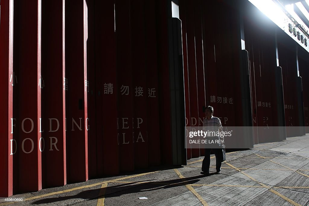 A man walks past a fire station in Hong Kong on August 15, 2014. Hong Kong lowered its annual economic growth forecast on August 15 after growth slowed to 1.8 per cent year-on-year in the second quarter.
