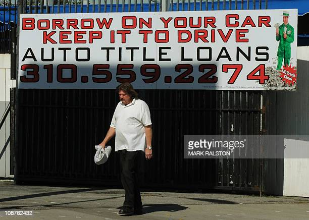 A man walks past a firm offering cash loans which use your car as collateral in Los Angeles on February 02 2011 The United States is poised to hit...