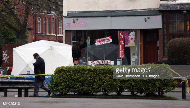 A man walks past a forensic tent at the scene in Old Trafford Greater Manchester where an 18 year old was stabbed to death yesterday