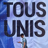 A man walks past a giant poster which translates as 'ALL UNITED' and diplayed in tribute to the victims of the deadly Nice attack on Bastille day on...