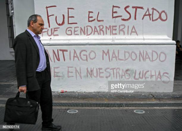 A man walks past a graffiti reading 'It was the State' while people demonstrate at the Plaza de Mayo square in Buenos Aires on October 18 a day after...