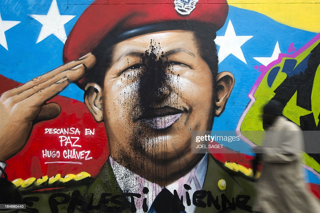 A man walks past a graffiti representing Venezuela's late president Hugo Chavez on March 26, 2013 in Paris. AFP PHOTO/ JOEL SAGET