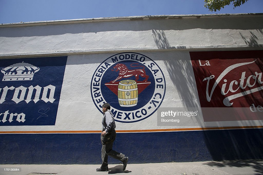 A man walks past a Grupo Modelo SAB logo painted on a wall outside the company's brewery in Mexico City, Mexico, on Thursday, June 6, 2013. Heineken NV and Grupo Modelo SAB, the dominant brewers in Mexico with brands such as Dos Equis and Corona, are nearing the end of an almost three-year-old government antitrust probe. Photographer: Susana Gonzalez/Bloomberg via Getty Images