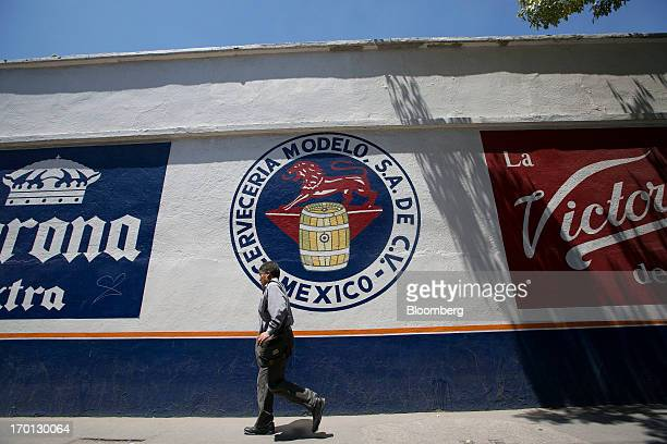 A man walks past a Grupo Modelo SAB logo painted on a wall outside the company's brewery in Mexico City Mexico on Thursday June 6 2013 Heineken NV...