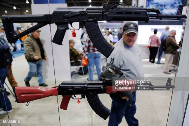 A man walks past a gun display at a National Rifle Association outdoor sports trade show on February 10 2017 in Harrisburg Pennsylvania / AFP /...