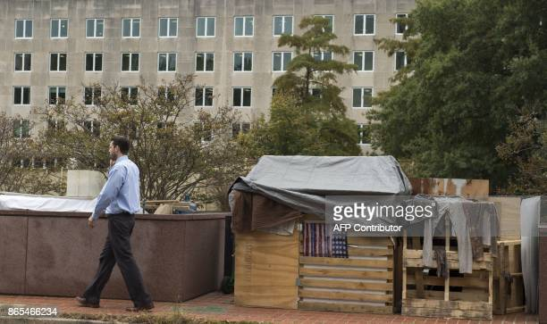 A man walks past a homeless person's shelter near the US Department of State on October 23 2017 / AFP PHOTO / Andrew CABALLEROREYNOLDS